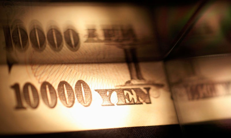 Light is cast on a Japanese 10,000 yen note as it's reflected in a plastic board in Tokyo, in this picture illustration